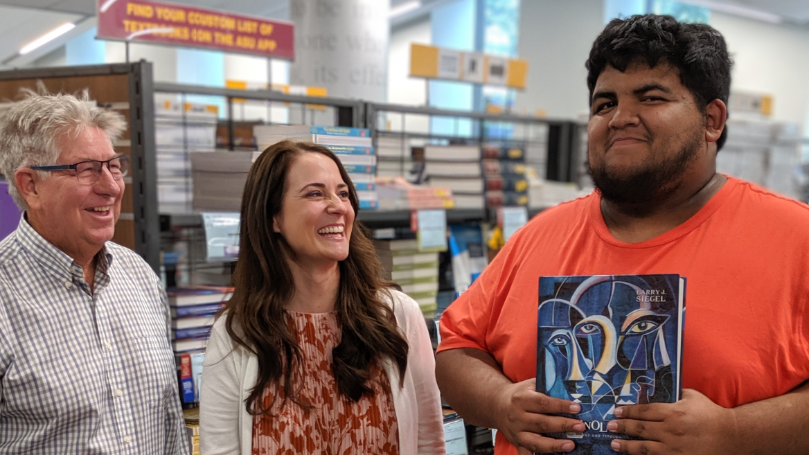 Representatives from ASU Bookstores and Follett (man and woman) smile with student Allan Valles Sanchez while he holds up a criminology and criminal justice textbook