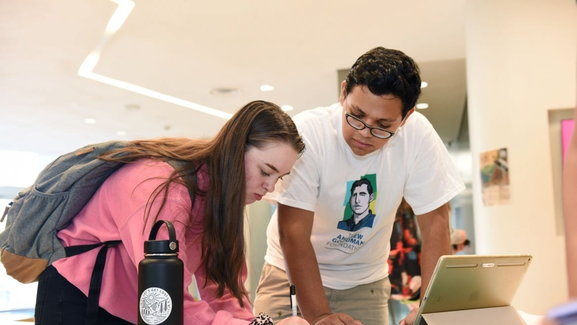 Andrew Goodman Ambassador Cyrus Commissariat, right, assists a student voter.
