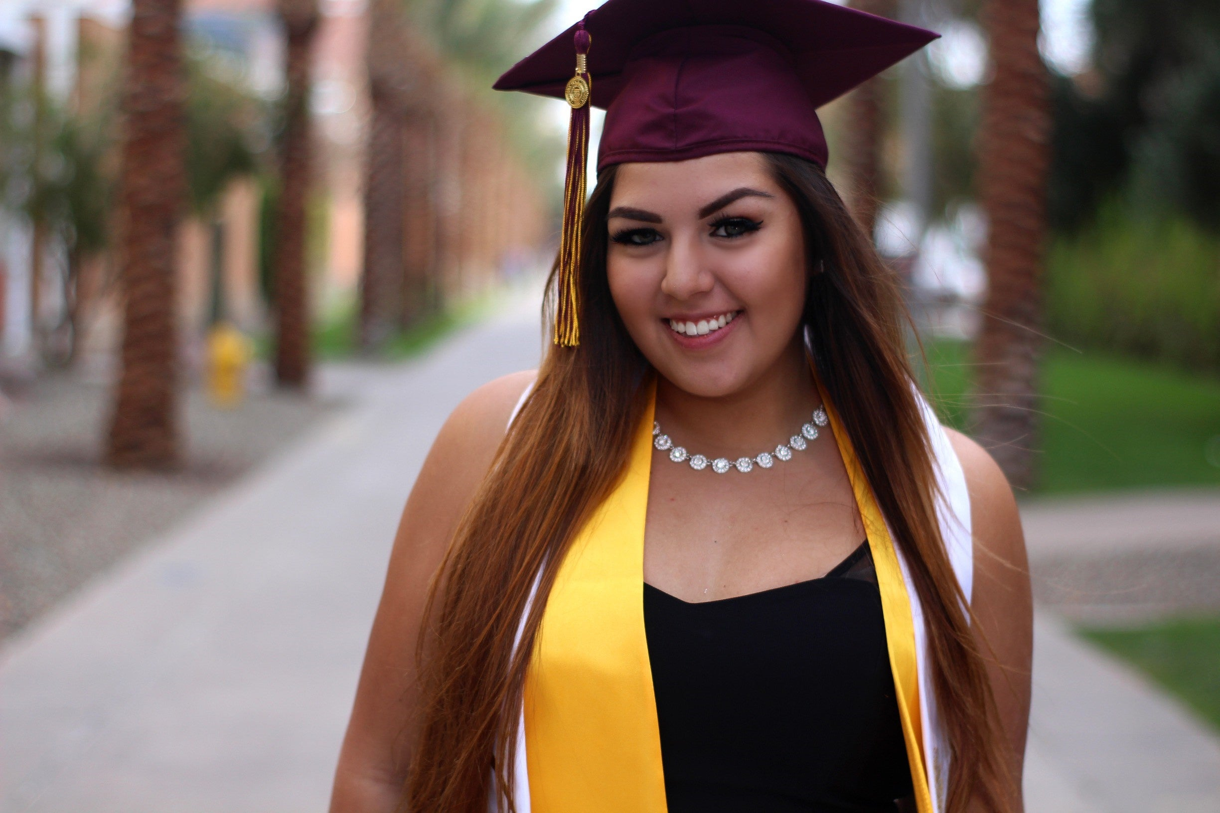 Diana Lizcano Hernandez in grad cap and stole in front of Tempe campus Palm Walk
