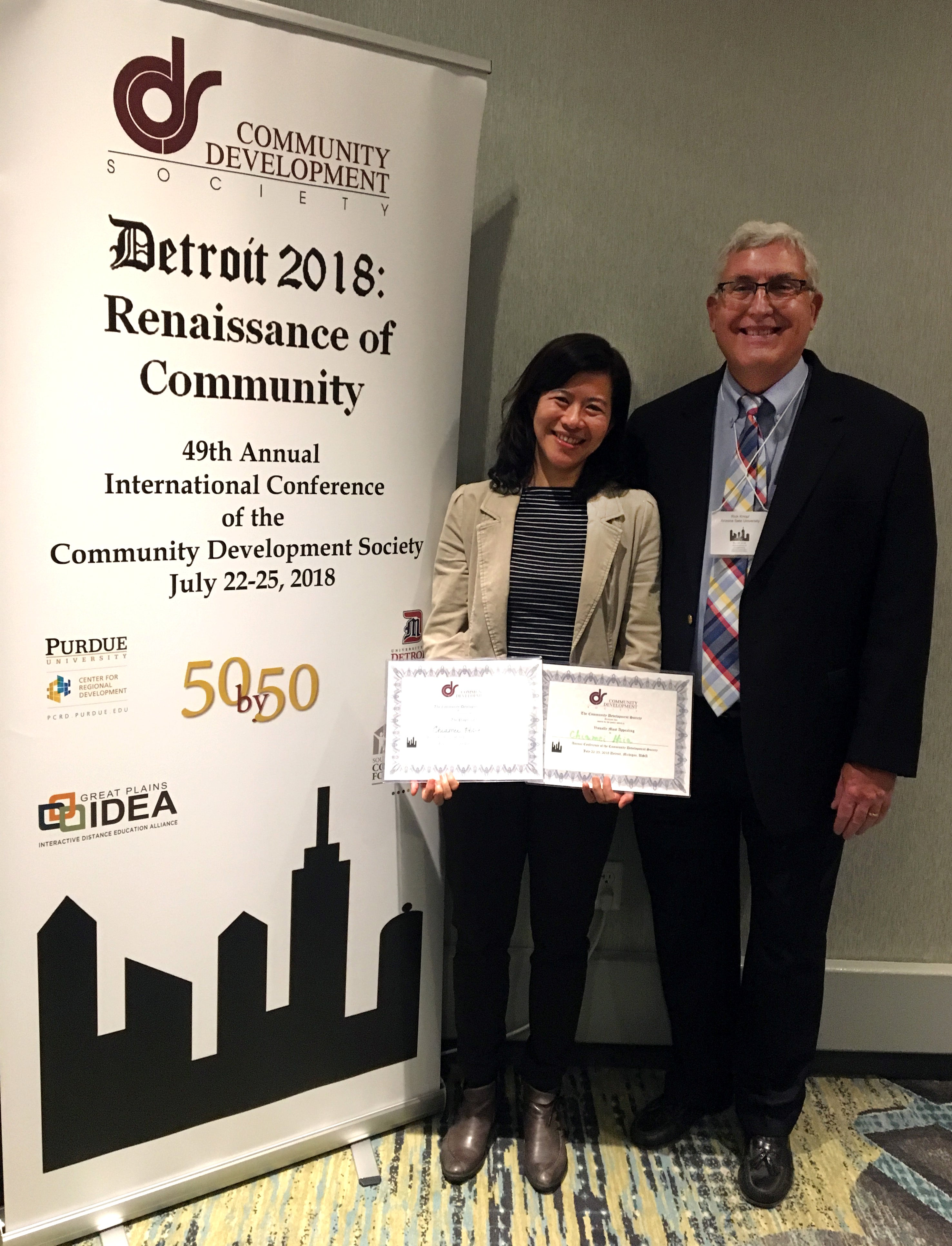 Chiamei Hsia stands with Richard Knopf in front of conference banner holding her awards