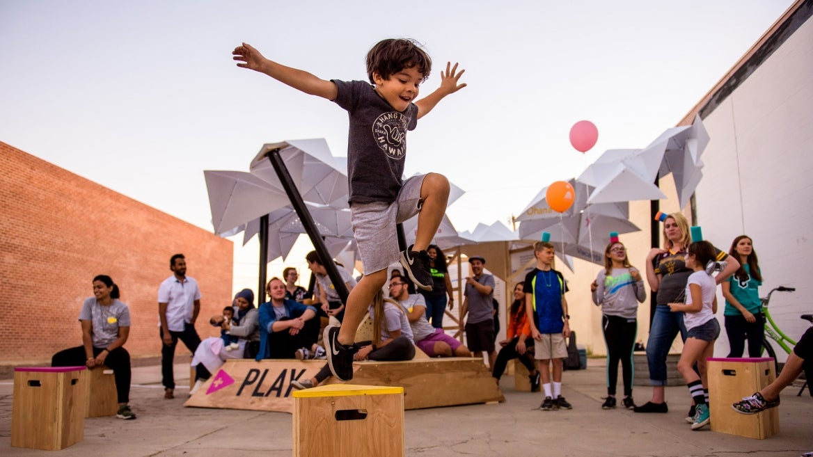 child standing on box dancing