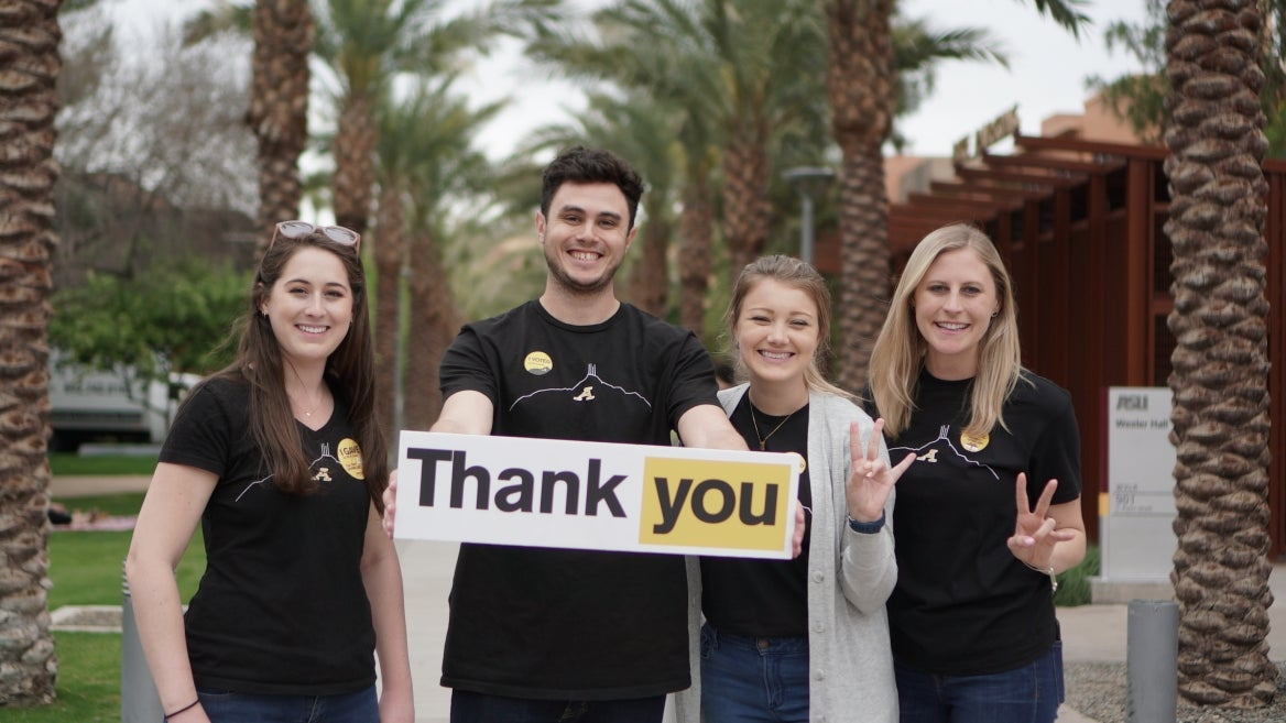 Four people hold a thank you sign to show support of Sun Devil Giving Day