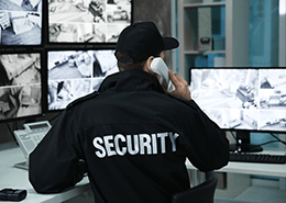 Security guard watching closed circuit TV monitors