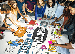 young adults surrounding a poster with volunteering icons